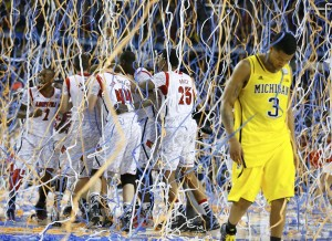 Michigan Burke walks off the court as Louisville celebrates defeating Michigan to win the NCAA men's Final Four championship basketball game in Atlanta