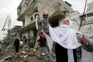 Palestinian woman shouts in front of houses in Rafah