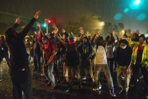 Protesters gesture as they stand in a street in defiance of a midnight curfew in Ferguson